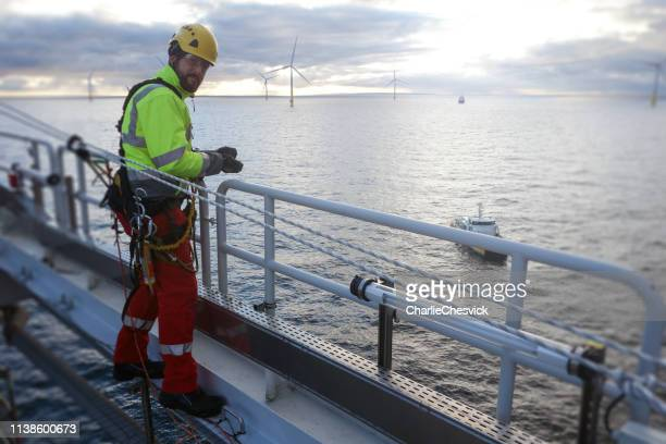 rope access technician making inspection and repairs of railing with transfer vessel guarding - oil rig stock pictures, royalty-free photos & images