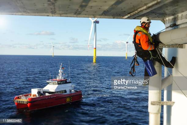 rope access technician making inspection, repairing on offshore platform with transfer vessel guarding - safety equipment stock pictures, royalty-free photos & images