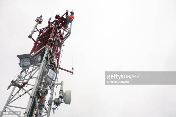 rope access technician working on top of the tower - antenna - high up stock photos and pictures