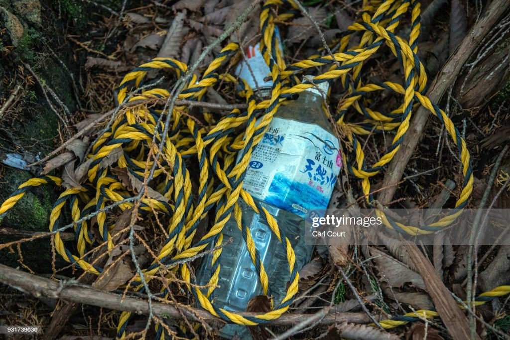 Rope and a bottle remain at the scene of an apparent suicide in Aokigahara forest, on March 14, 2018 in Fujikawaguchiko, Japan. Aokigahara forest lies on the on the northwestern flank of Mount Fuji and in recent years has become known as one of the world's most prevalent suicide sites. The density of the forest is believed to be a contributing factor with people often tying string to trees to find their way back to a path in case they change their mind. In 2010, officials recorded more than 200 attempted suicides in the forest with attempts said to increase during the end of the Japanese fiscal year. In recent years, local officials have stopped publicising the numbers in an attempt to decrease Aokigahara's association with suicide.