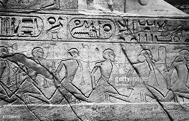A rope around the necks links these running slaves shown in a detail at the feet of one of the colossal statues of the Pharaoh at the entrance to the...