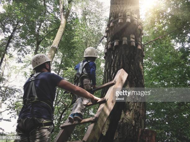 hochseilgarten klettern hindernis abenteuer teamarbeit - hoch position stock-fotos und bilder