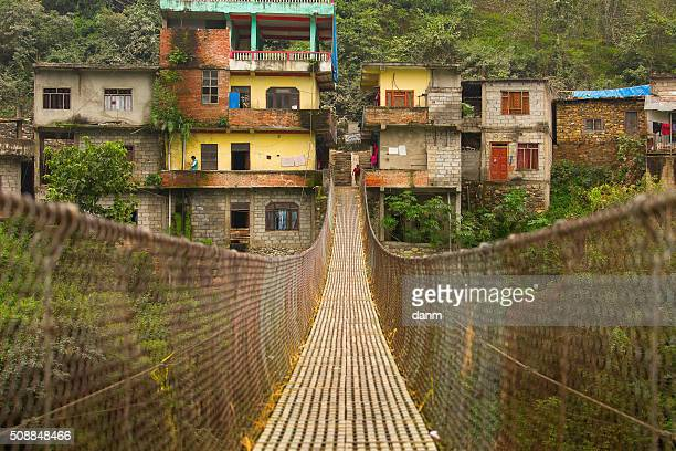 Rope hanging suspension bridge in Nepal with colorful village in bacground