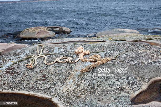 A rope spelling HATE on a rocky coastline