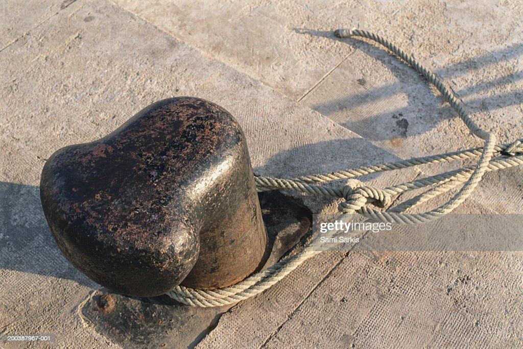 Rope tied around bollard, close-up : Stock Photo