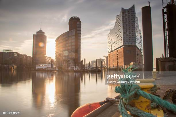rope tied on cleat at harbor against buildings during sunset - hamburg stock-fotos und bilder