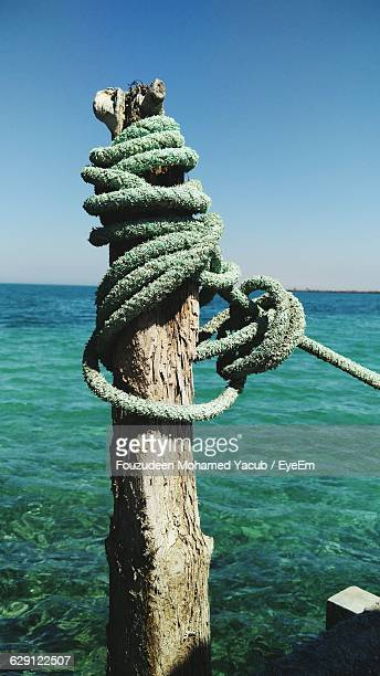 Rope Tied Up Of Wooden Post By Sea Against Clear Blue Sky