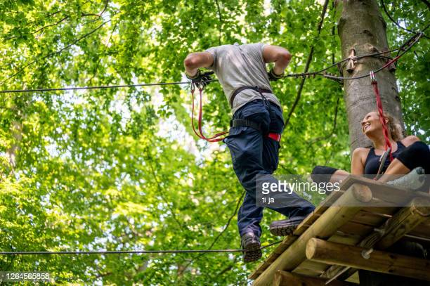rope walking at adventure park - active lifestyle stock pictures, royalty-free photos & images