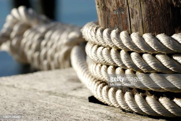 rope wound around a mooring bollards to hold a ship, symbolic image for security, stability and support, kiel, schleswig-holstein, germany - vertäut stock-fotos und bilder