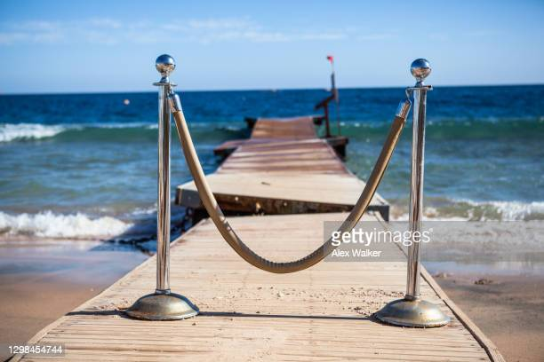 roped off pontoon jetty on beach. - cordon boundary stock pictures, royalty-free photos & images