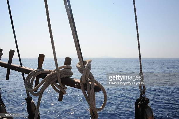 Ropes Tied To Wood Of Sailing Ship In Ocean Against Sky