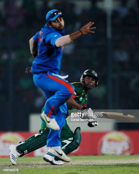 Roqibul Hassan of Bangladesh plays a shot as Virat Kohli of India attempts to take a catch during the opening game of the ICC Cricket World Cup...
