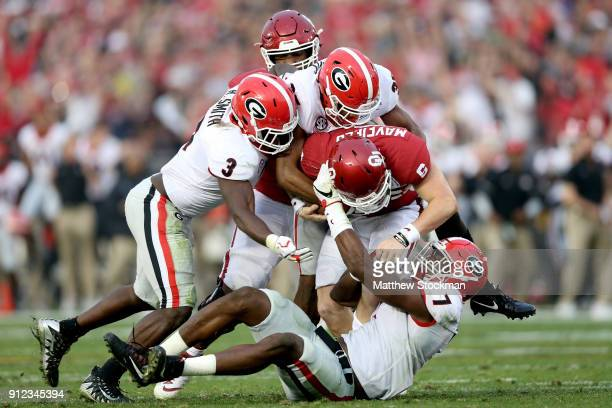 Roquan Smith Lorenzo Carter and Aaron Davis of the Georgia Bulldogs sack Baker Mayfield of the Oklahoma Sooners during the 2018 College Football...