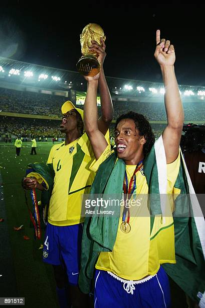 Roque Junior and Ronaldinho of Brazil lift the trophy after the Germany v Brazil World Cup Final match played at the International Stadium Yokohama...