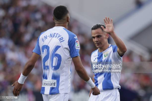 Roque Mesa of Deportivo Leganese clashes hands with his teammate Youssef En-Nesyri during the Liga match between CD Leganes and Club Atletico de...