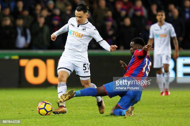 Roque Mesa of Swansea City avoids a slide tackle by Jeffrey Schlupp of Crystal Palace during the Premier League match between Swansea City and...