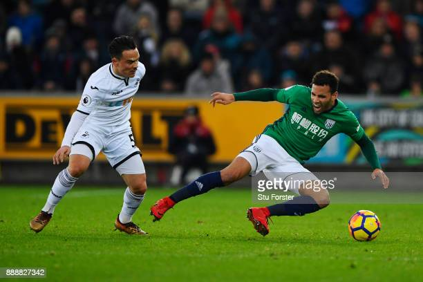 Roque Mesa of Swansea City fouls Hal RobsonKanu of West Bromwich Albion during the Premier League match between Swansea City and West Bromwich Albion...
