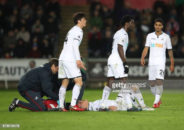 Roque Mesa of Swansea City receives treatment from the medical team with a head injury during the Premier League match between Swansea City and AFC...
