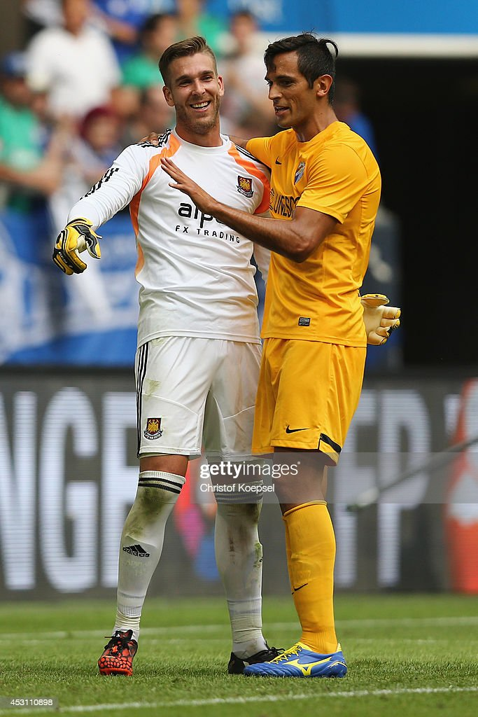 Roque Santa Cruz of Malaga (R) embraces Adrian of West Ham United (L) after winning 2-0 the match between FC Malaga and West Ham United as part of the Schalke 04 Cup Day at Veltins-Arena on August 3, 2014 in Gelsenkirchen, Germany.