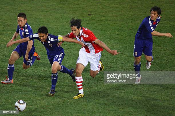 Roque Santa Cruz of Paraguay challenged by Yuto Nagatomo Makoto Hasebe and Shinji Okazaki during the 2010 FIFA World Cup South Africa Round of...