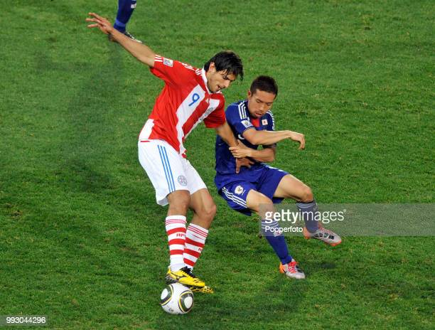 Roque Santa Cruz of Paraguay holds off the challenge of Yuto Nagatomo of Japan during a FIFA World Cup Round of 16 match at the Loftus Versfeld...