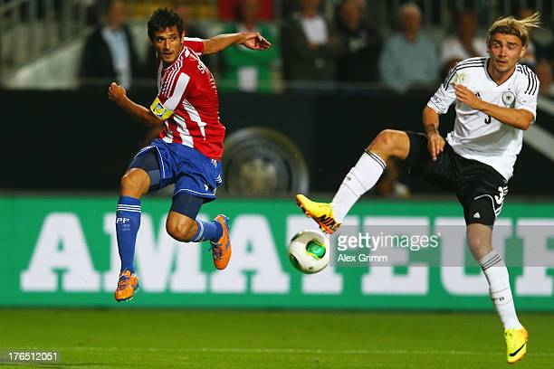Roque Santa Cruz of Paraguay is challenged by Marcel Schmelzer of Germany during the international friendly match between Germany and Paraguay at...