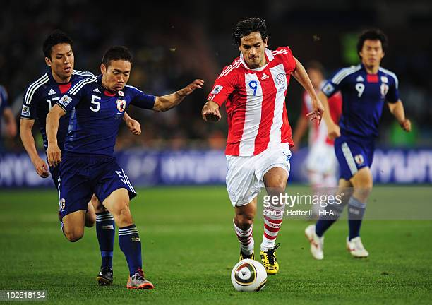 Roque Santa Cruz of Paraguay runs with the ball under pressure from Yuto Nagatomo of Japan during the 2010 FIFA World Cup South Africa Round of...