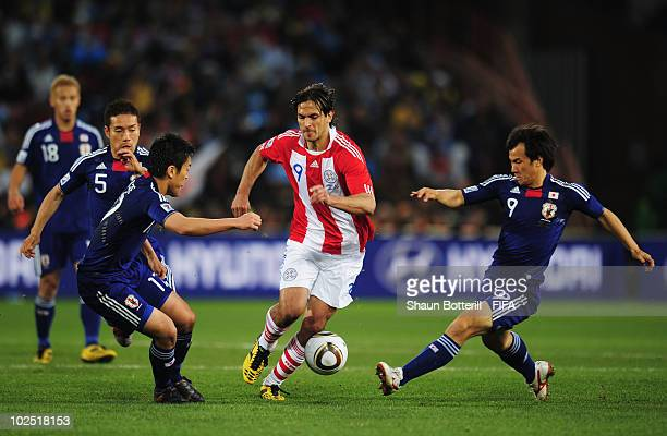 Roque Santa Cruz of Paraguay runs with the ball under pressure from Shinji Okazaki of Japan during the 2010 FIFA World Cup South Africa Round of...