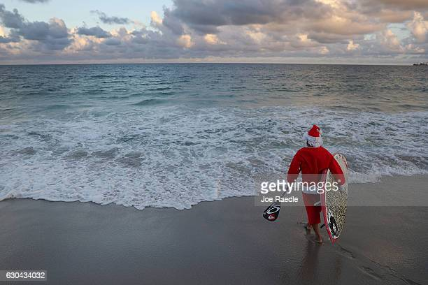 Roray Kam dressed as Santa Claus enjoys the surf on his standup paddle board on December 22 2016 in Fort Lauderdale Florida South Florida is expected...