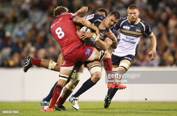 Rory Arnold of the Brumbies is tackled by Scott Higginbotham of the Reds during the round seven Super Rugby match between the Brumbies and the Reds...