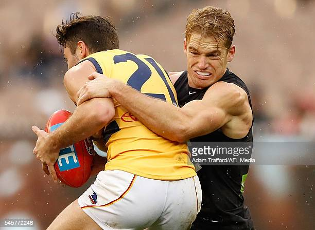 Rory Atkins of the Crows is tackled by Sam Kerridge of the Blues during the 2016 AFL Round 16 match between the Carlton Blues and the Adelaide Crows...