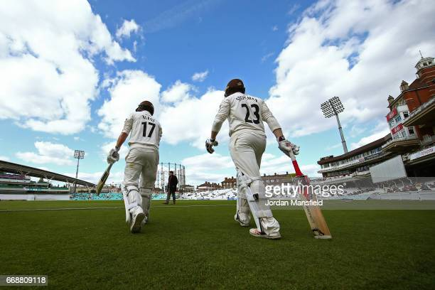 Rory Burns and Mark Stoneman of Surrey make their way onto the field to start the Surrey first innings during day two of the Specsavers County...