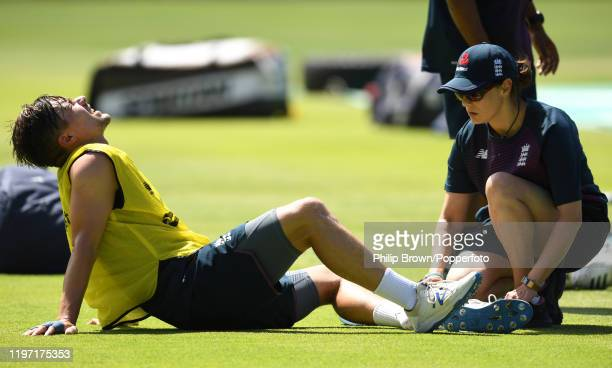 Rory Burns of England on the ground after injuring his ankle in a game of football with doctor Anita Biswas attending during a training session at...