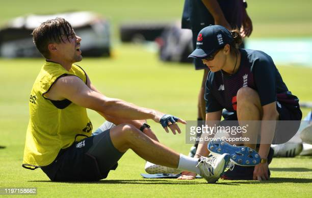 Rory Burns of England throws away his shoe after injuring his ankle in a game of football with doctor Anita Biswas attending during a training...
