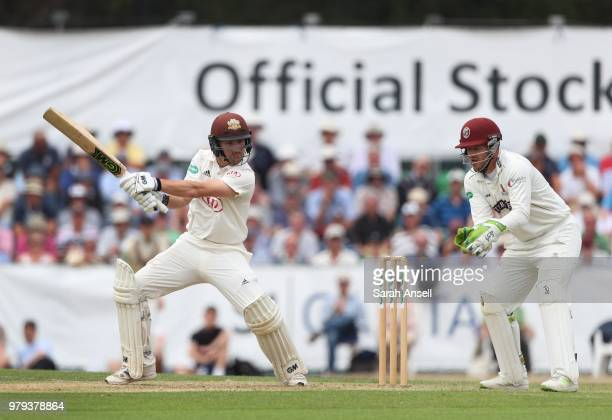 Rory Burns of Surrey hits a boundary as Somerset wicket keeper Steven Davies during day 1 of the Specsavers County Championship Division One match...