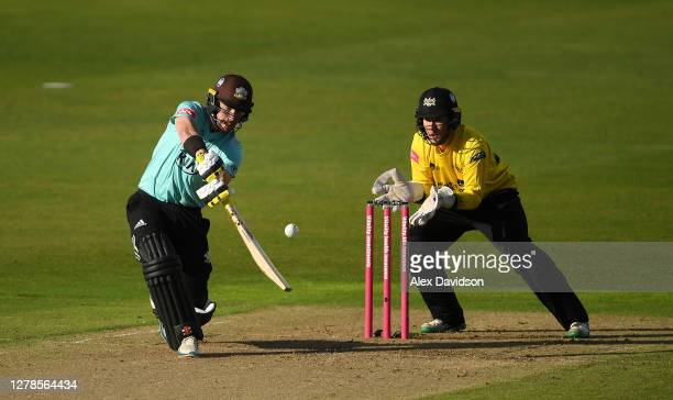 Rory Burns of Surrey hits runs watched on by James Bracey of Gloucestershire during the Vitality Blast 2020 Semi Final match between Surrey and...