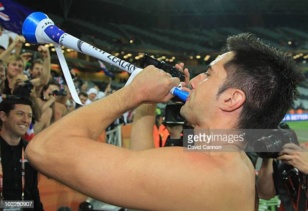 Rory Fallon of New Zealand blows a vuvuzela as he celebrates with New Zealand fans after holding Italy to a draw in the 2010 FIFA World Cup South...