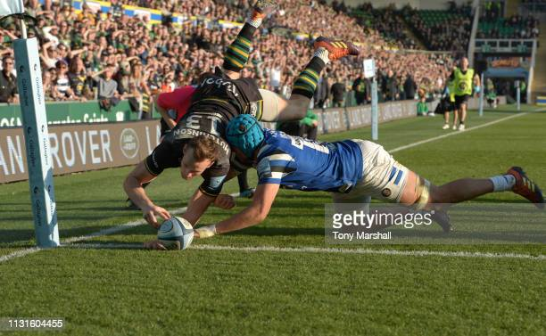 Rory Hutchinson of Northampton Saints is tackled by Zach Mercer of Bath Rugby as he dives in to score a try during the Gallagher Premiership Rugby...