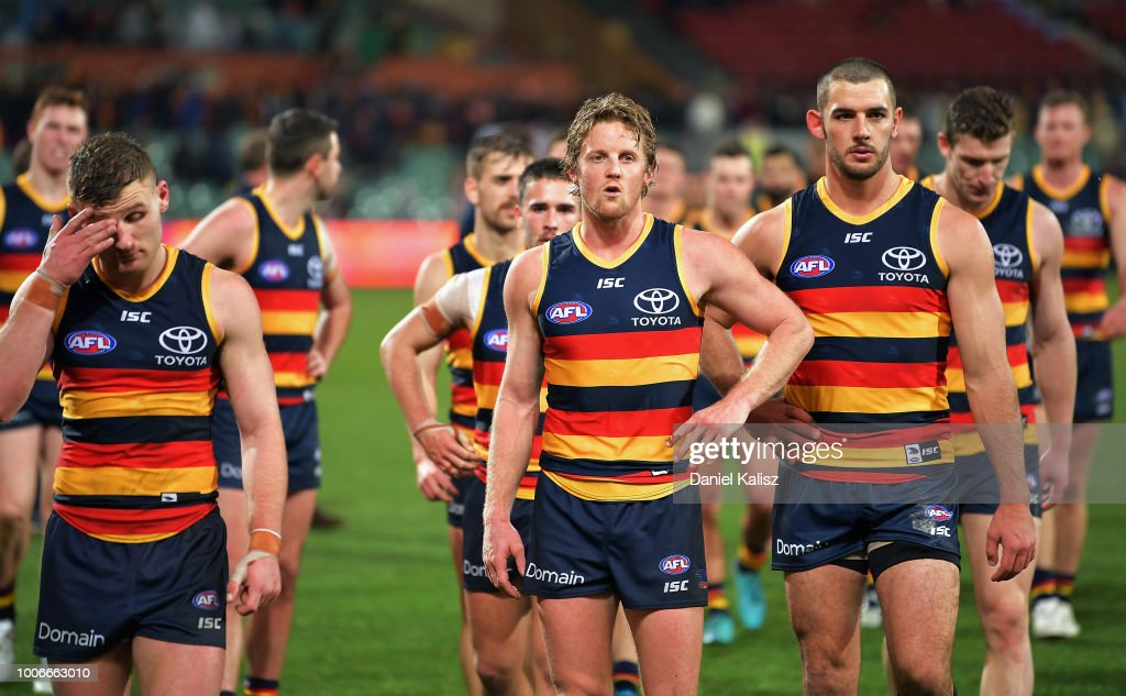Rory Laird of the Crows, Rory Sloane of the Crows and Taylor Walker of the Crows look on dejected after the final siren during the round 19 AFL match between the Adelaide Crows and the Melbourne Demons at Adelaide Oval on July 28, 2018 in Adelaide, Australia.