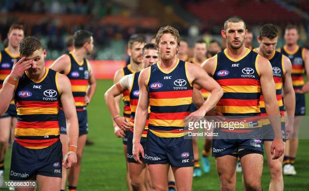 Rory Laird of the Crows Rory Sloane of the Crows and Taylor Walker of the Crows look on dejected after the final siren during the round 19 AFL match...