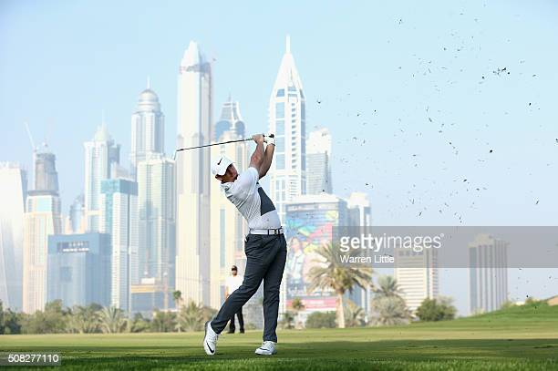 Rory McIlory of Northern Ireland plays his second shot into the 13th green during the first round of the Omega Dubai Desert Classic on the Majlis...