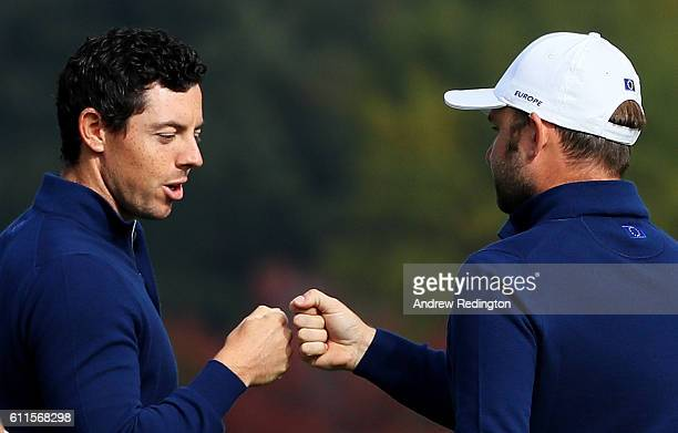 Rory McIlroy and Andy Sullivan of Europe react on the 12th green during morning foursome matches of the 2016 Ryder Cup at Hazeltine National Golf...