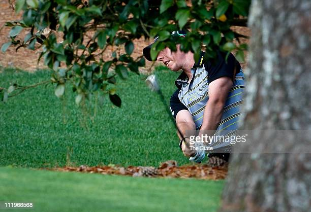 Rory McIlroy hits his third shot from behind a bush on the 10th green during the final round of the Masters Tournament at Augusta National Golf Club...