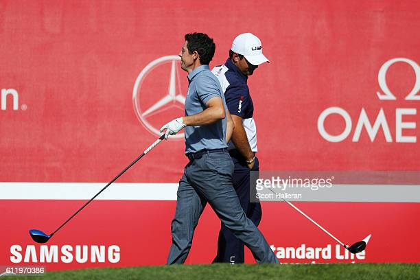 Rory McIlroy of Europe and Patrick Reed of the United States pass each other on the first tee during singles matches of the 2016 Ryder Cup at...