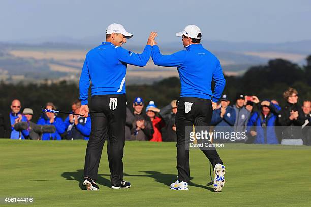Rory McIlroy of Europe celebrates a putt on the 8th green with Sergio Garcia of Europe during the Afternoon Foursomes of the 2014 Ryder Cup on the...