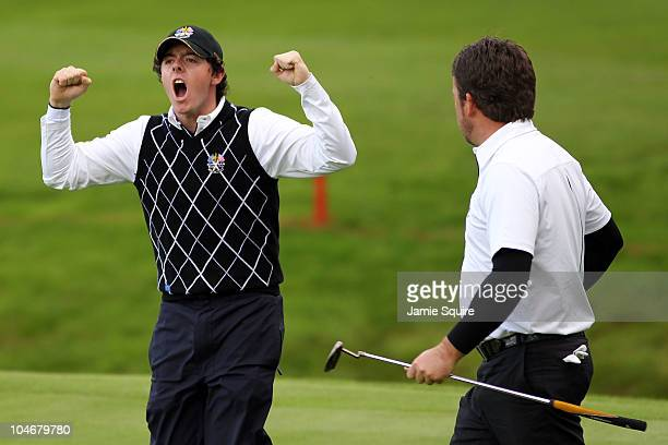Rory McIlroy of Europe celebrates after team mate Graeme McDowell holed a putt on the 15th green during the Fourball & Foursome Matches during the...