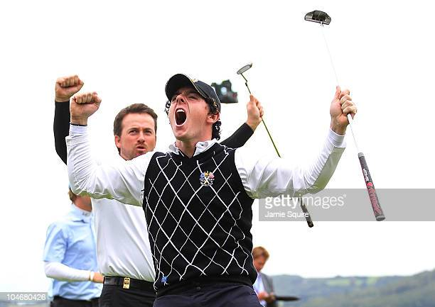 Rory McIlroy of Europe celebrates holing a putt with team mate Graeme McDowell to wiin their match on the 17th green during the Fourball & Foursome...