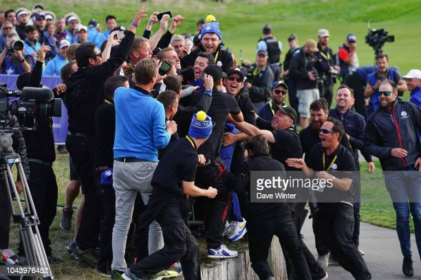 Rory McIlroy of Europe celebrates with the greenkeepers after his side wins during Day Three of the 2018 Ryder Cup at Le Golf National on September...