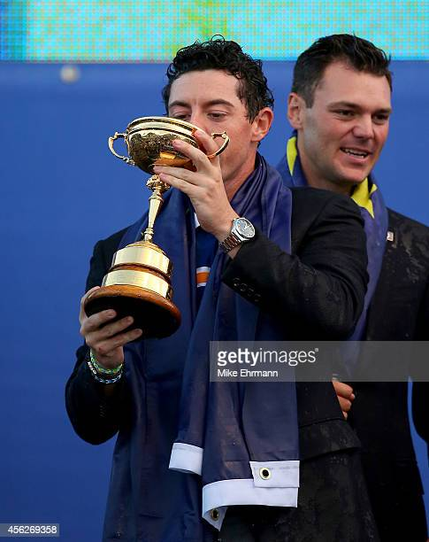 Rory McIlroy of Europe celebrates with the Ryder Cup trophy after the Singles Matches of the 2014 Ryder Cup on the PGA Centenary course at the...