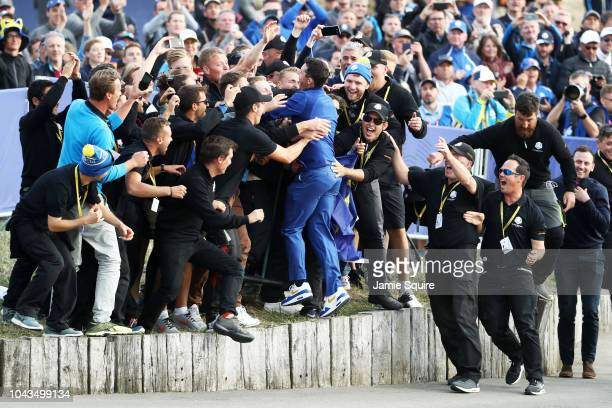 Rory McIlroy of Europe jumps into the crowd as he celebrates after winning The Ryder Cup during singles matches of the 2018 Ryder Cup at Le Golf...